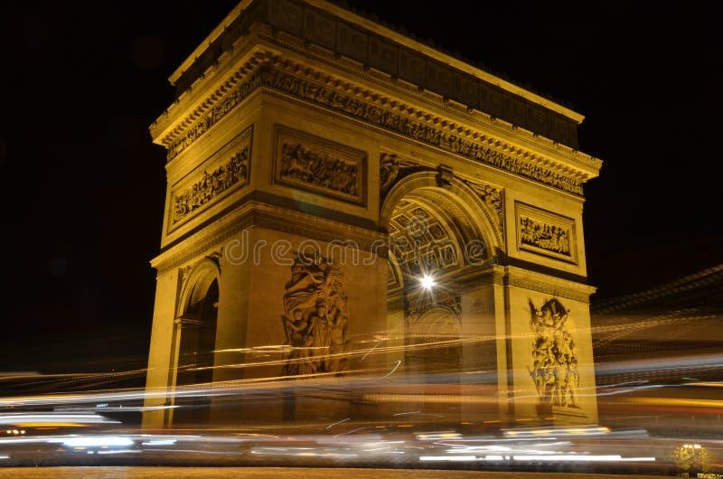 Arc de Triomphe en París, Francia - vista nocturna con los rastros de luces de los coches imagen de archivo