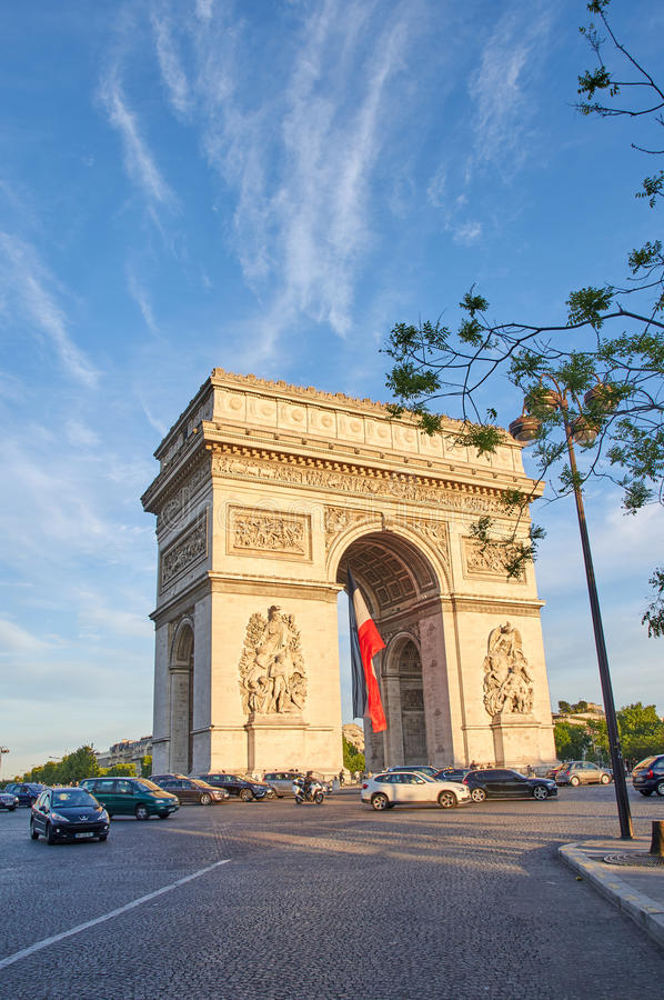 Arc de Triomphe. PARIS, FRANCE - MAY 10, 2017 : Arc de Triomphe with french flag in the evening. Triumphal Arch is one of the most famous monuments in Paris stock images