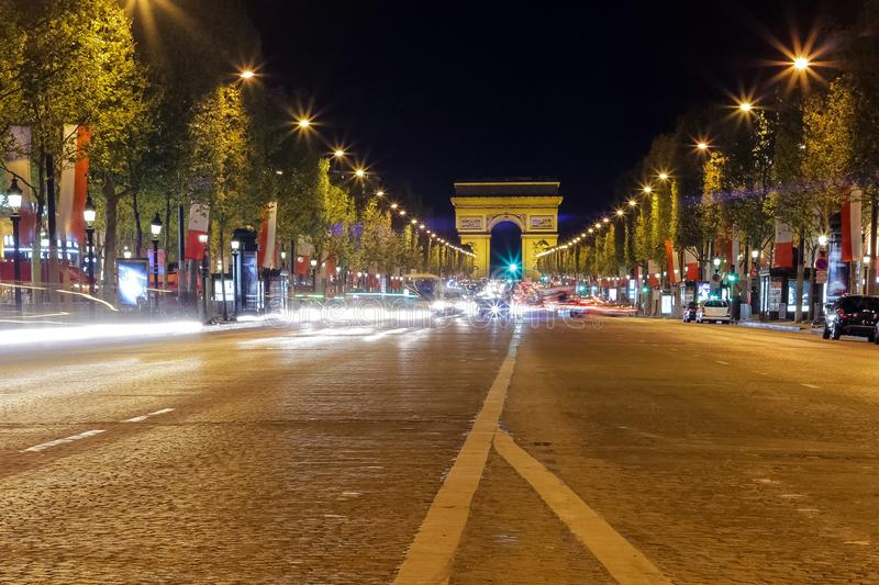 Arc de triomphe in Paris, France during rush hour at night. Traffic lights, tourist attraction royalty free stock photos