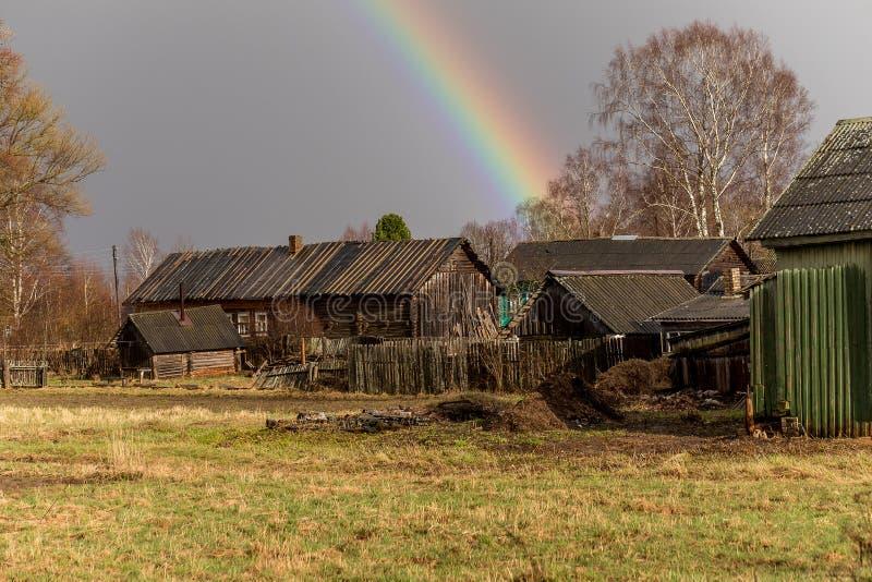 Arc-en-ciel après pluie au-dessus de la route et du vieux village image libre de droits