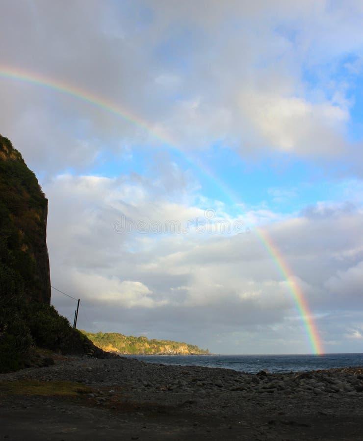Arc-en-ciel au-dessus de ciel bleu et océan lumineux et plage rocheuse photos libres de droits