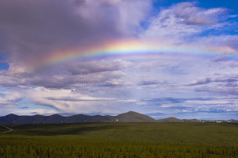 Arc-en-ciel au-dessus des montagnes de route et de Richardson de Dempster images stock
