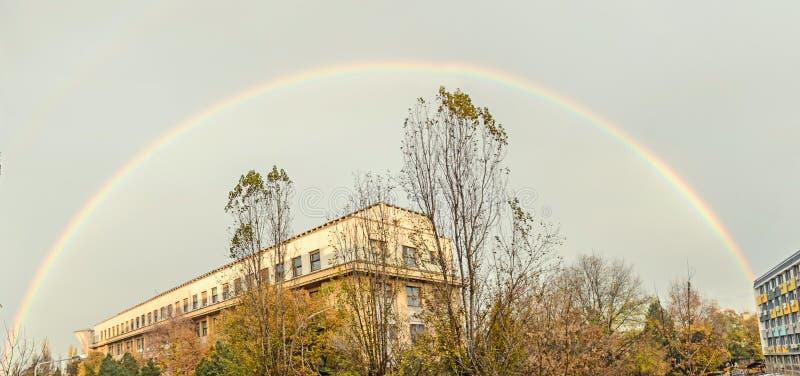Arc-en-ciel coloré vibrant au-dessus de ciel nuageux bleu, ville européenne image libre de droits