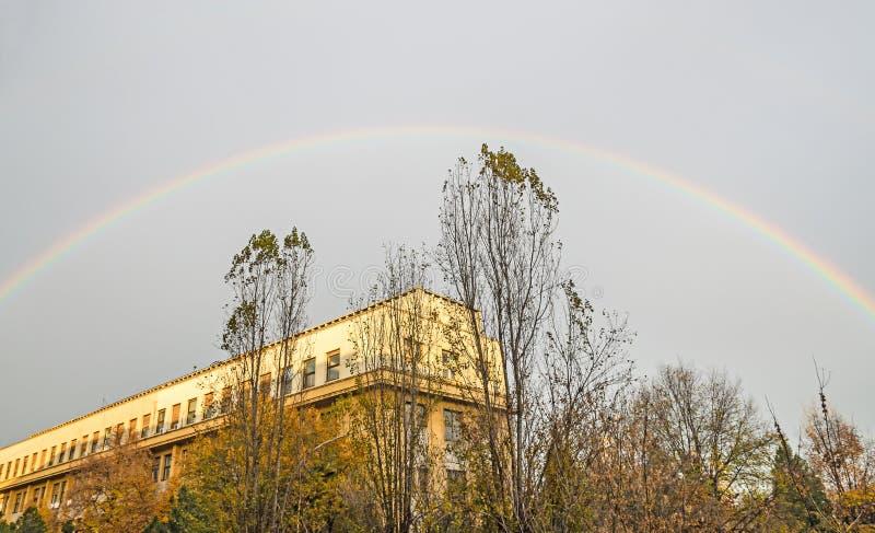 Arc-en-ciel coloré vibrant au-dessus de ciel nuageux bleu, ville européenne photo libre de droits