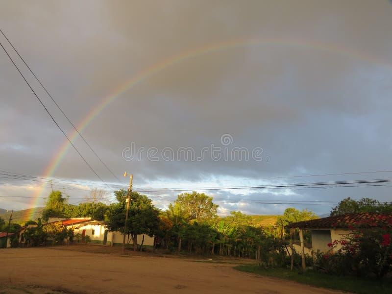 Arc-en-ciel dans le coucher du soleil de village photo libre de droits