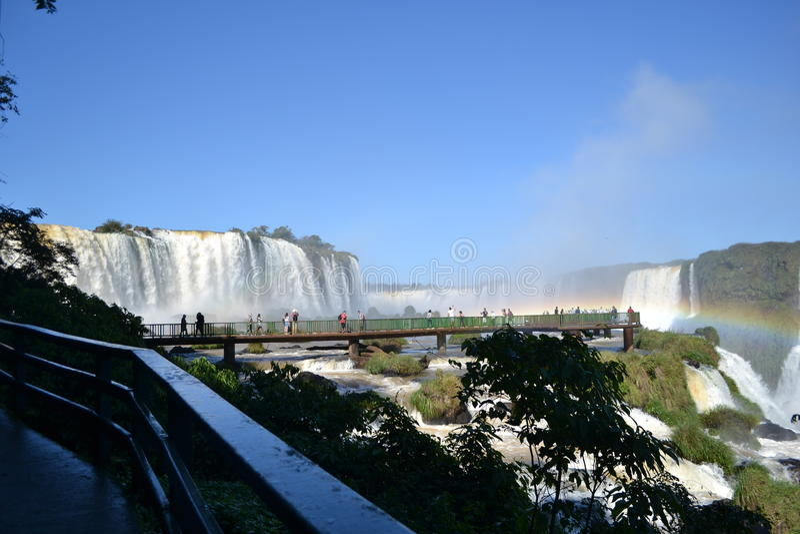 Arc-en-ciel de cascades d'Iguazu sur le ciel ensoleillé et bleu et le pont photos stock