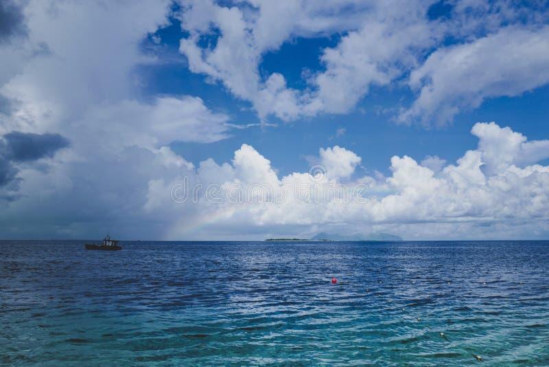 Arc-en-ciel léger au-dessus de l'océan, du bord de mer d'horizon, du ciel bleu et du cloudscape photos libres de droits