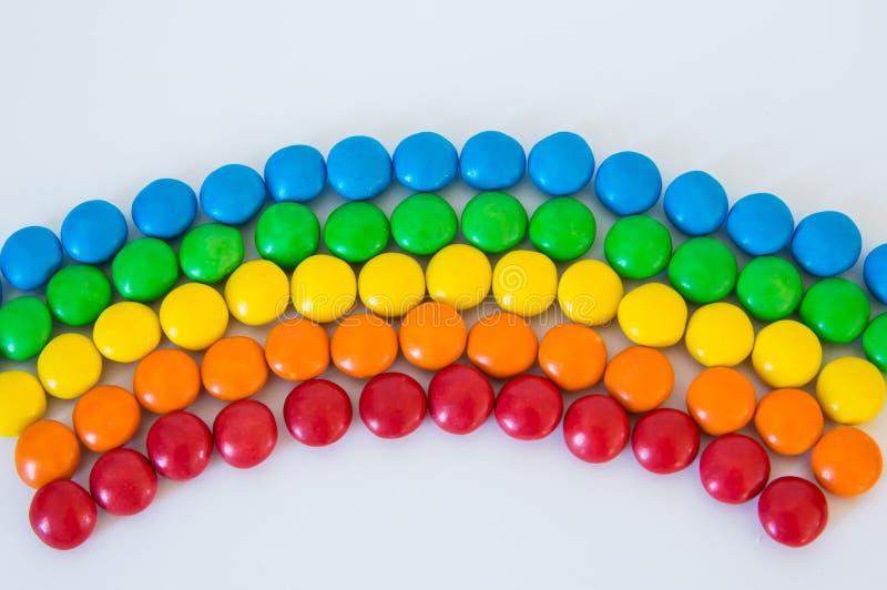 Arc-en-ciel multicolore fait de mensonges colorés ronds de bonbons à dragée sur un fond blanc image libre de droits