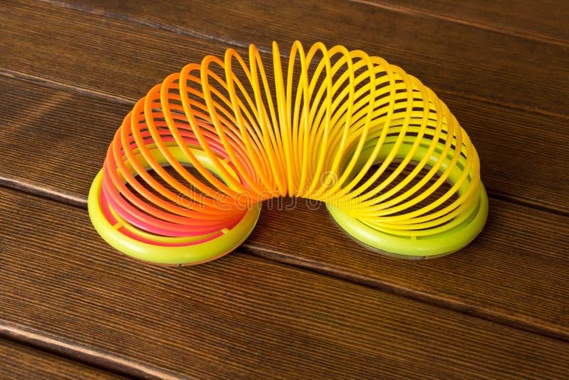 Arc-en-ciel en plastique de jouet sur une table en bois Spirale multicolore pour photo stock