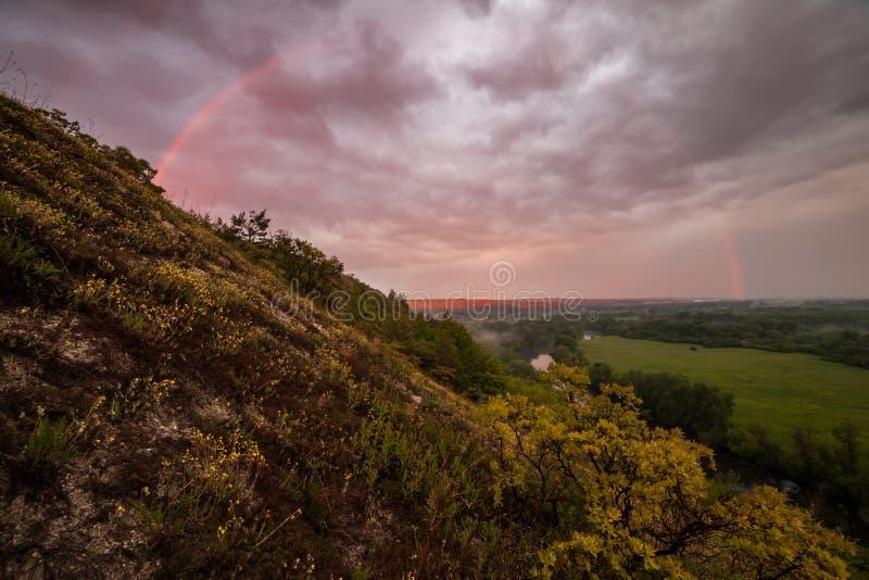 Arc-en-ciel sur le lever de soleil au-dessus de la vallée photo stock