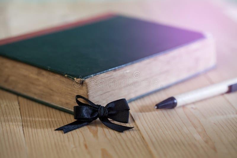 Arc noir avec le ruban avec le vieux livre sur la table photo stock