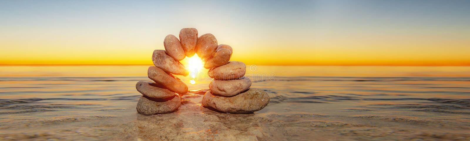 Arc with pebbles. In water at a beautiful sunset royalty free stock image