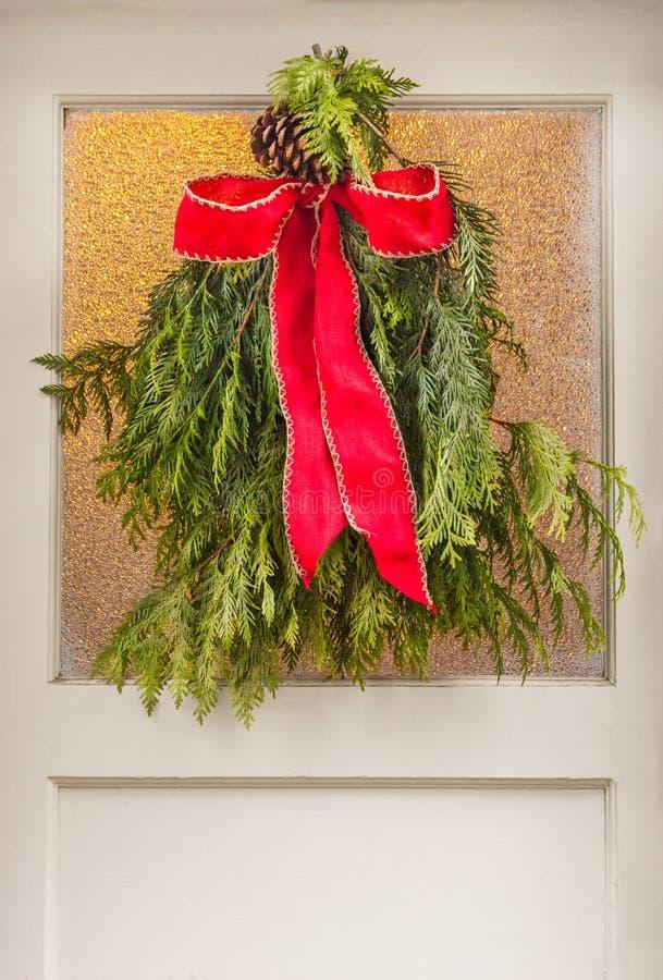 Arc rouge de style de cru attaché à la guirlande à feuilles persistantes de Noël images libres de droits