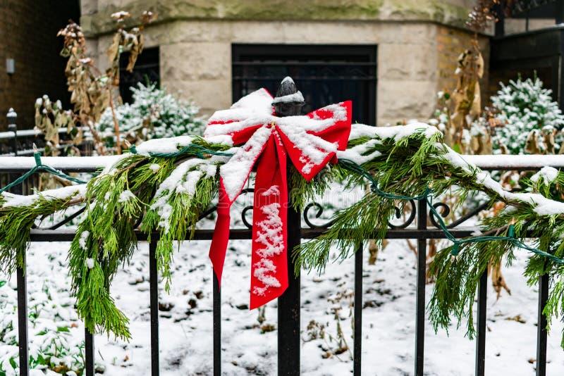 Arc rouge de vacances sur une barrière de jardin enveloppée avec une guirlande et des lumières de pin pendant l'hiver avec la nei images libres de droits