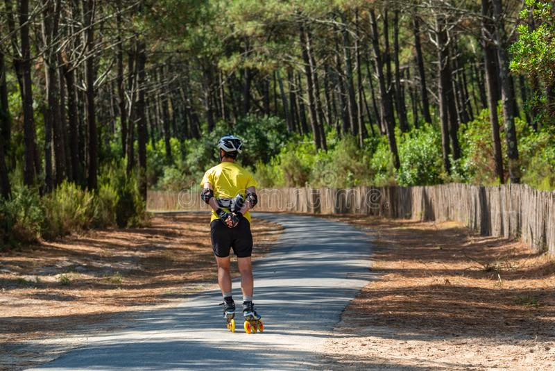 Arcachon Bay, France. Bike path in the pine forest. A man on a bike path in the pine forest royalty free stock photos