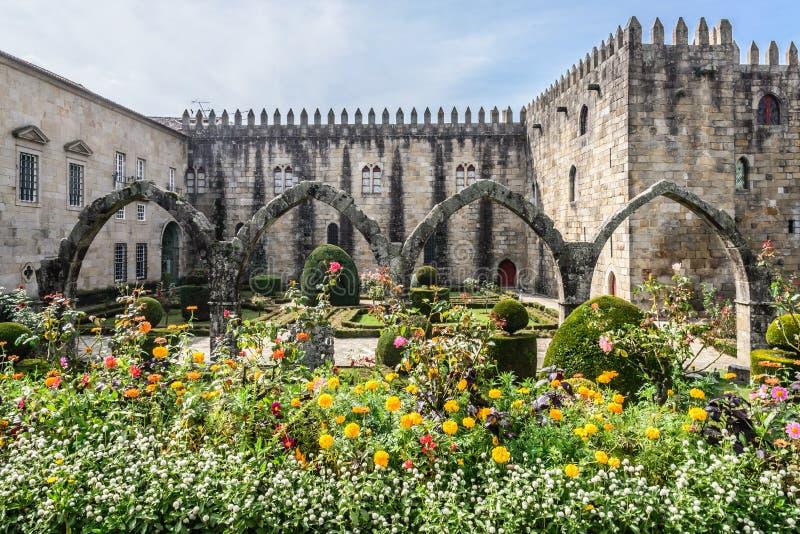 Arcada de piedra en el jardín de flores imagenes de archivo