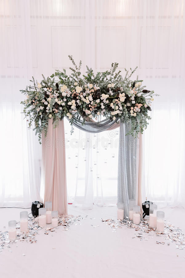 Arcada hermosa de la boda Arco adornado con el paño y las flores amelocotonados y plateados fotos de archivo
