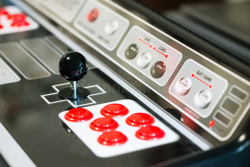 Arcade joystick. Detail of a black joystick and red buttons on an arcade game machine stock images