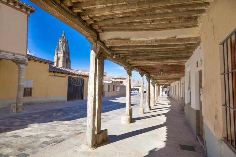 Medieval arcaded street and church tower in Ampudia old town. Arcaded buildings, in medieval street, landmark and monument from seventeenth century, and church royalty free stock photography
