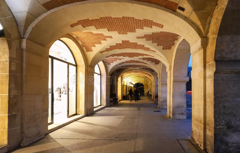 The arcades of place des Vosges in Paris , France. The arcades of place des Vosges, Paris, France. The houses fronts are all built to the same design of red stock image