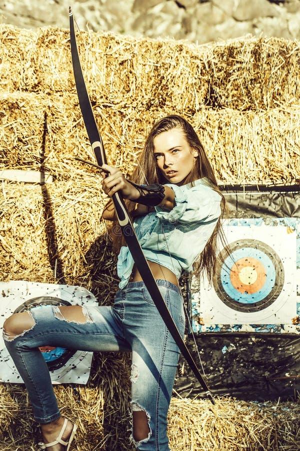 Arcere grazioso della ragazza che tende su con l'arco e la freccia fotografie stock