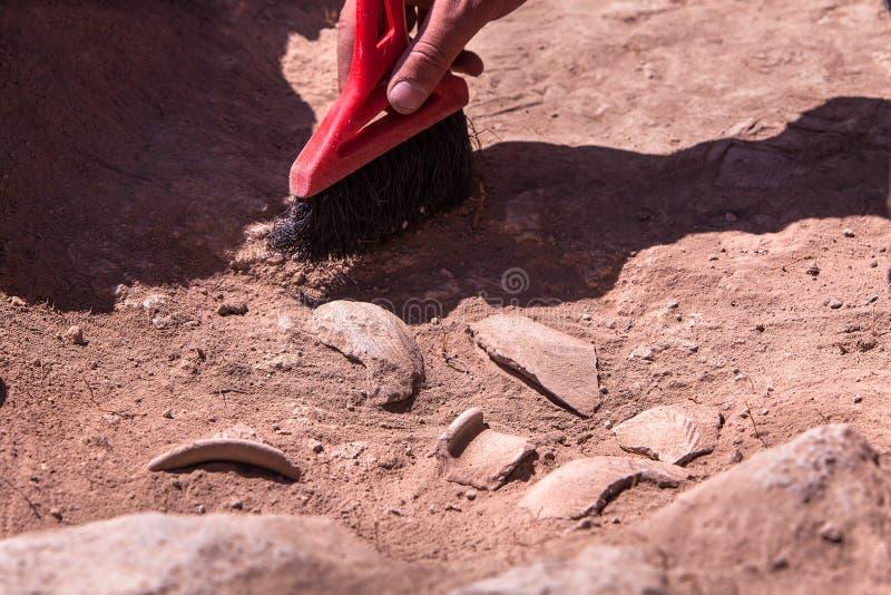 Archäologe, der an Standort, Hand mit Bürste arbeitet stockbilder