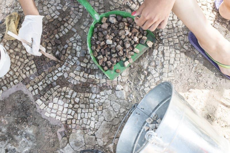 Archäologen stellen Artefaktmosaik wieder her lizenzfreie stockbilder