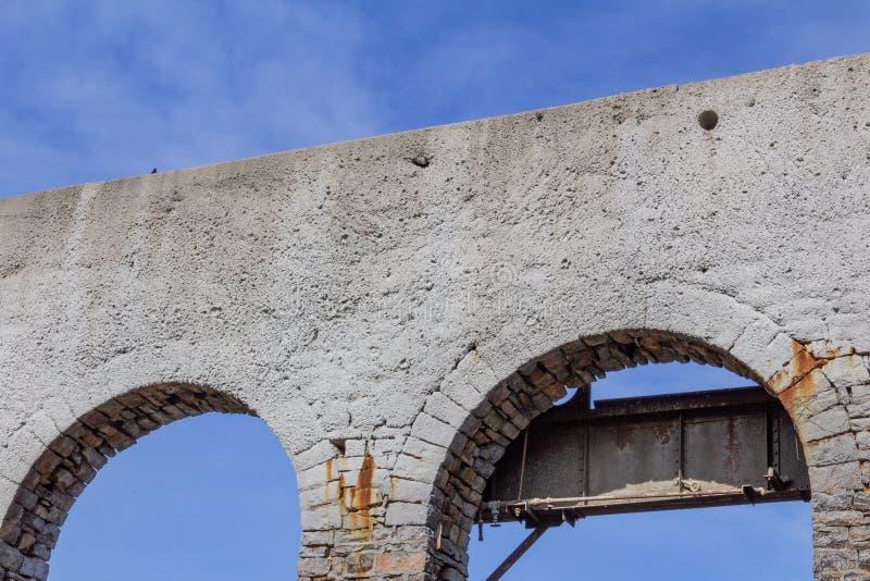 Arché aperti del mattone da una costruzione abbandonata, bianca con metallo arrugginito contro un cielo blu immagine stock