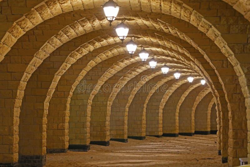 Arché che formano un modo della passeggiata sotto un pilastro acceso alla notte immagine stock libera da diritti