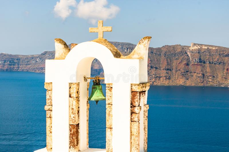 Arch with a bell, white houses and church with blue domes in Oia village. Island Santorini, Greece stock photography