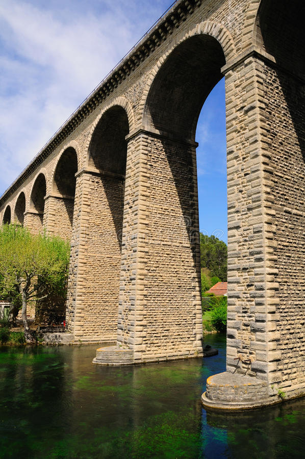 Arch bridge. Huge arch bridge built over Sorgue river in southeastern France stock image