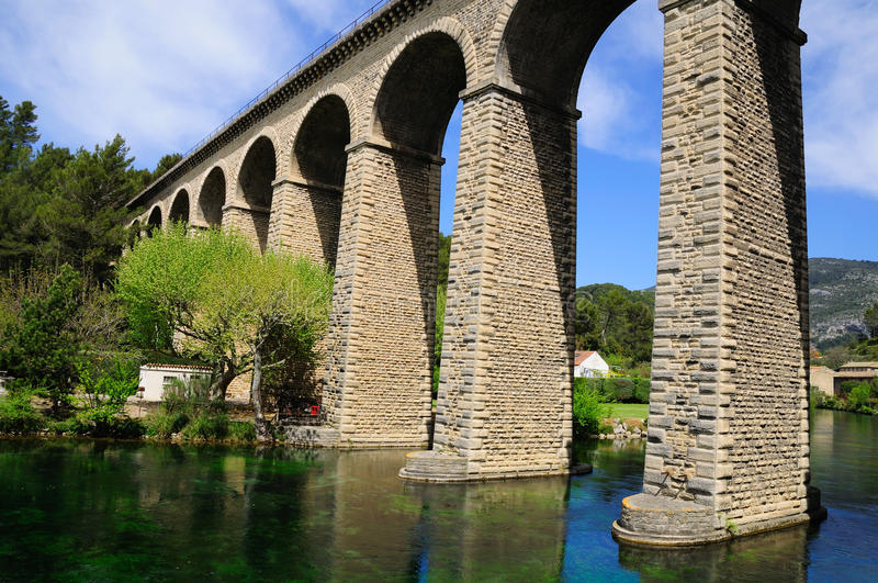 Arch bridge. Huge arch bridge built over Sorgue river in southeastern France royalty free stock images