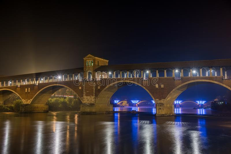 Arch bridge with lights at night time in Pavia, Italy. An arch bridge with lights at night time in Pavia, Italy royalty free stock photography