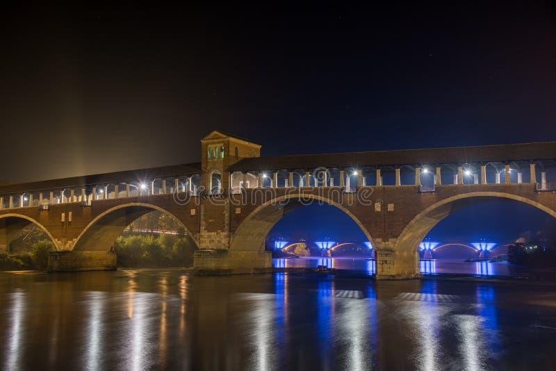 Arch bridge med ljus nattetid i Pavia, Italien royaltyfri fotografi