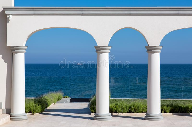 An arch with columns of white stone and a marble floor. stock image