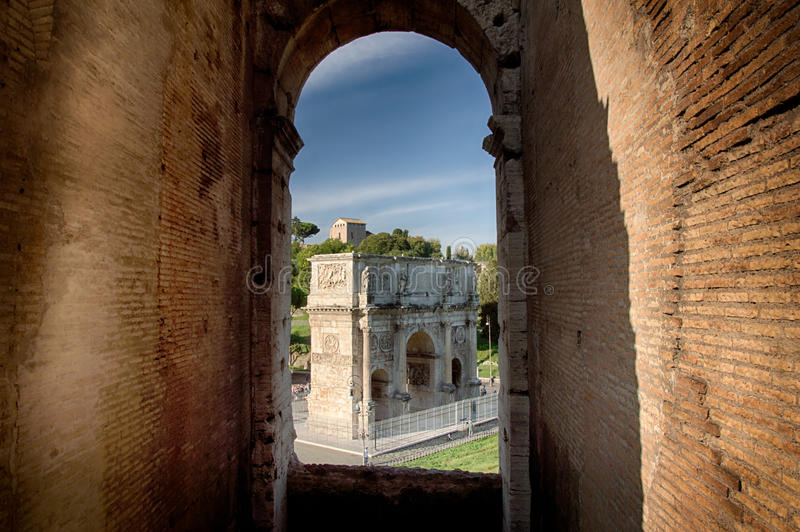 The Arch of Constantin. View of the Arch of Constantin through a arching window of the roman colosseum royalty free stock images