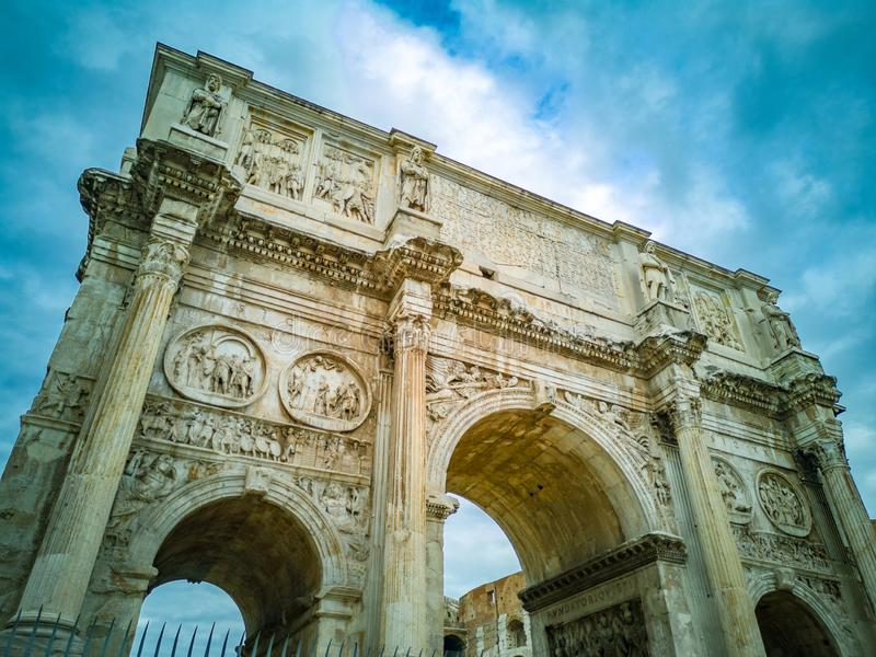 The Arch of Constantine Italian: Arco di Costantino. Triumphal arch in Rome, situated between the Colosseum and the Palatine Hill. Blue sky with clouds in the stock photography