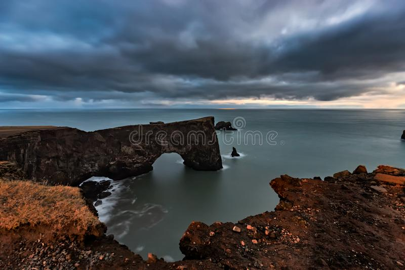 Arch at Dyrholaey in Iceland at sunset. The Dyrholaey arch in Soth Iceland near the town/village of Vik on a cloudy evening stock photos