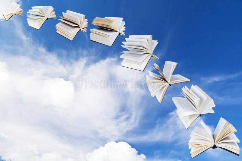 Arch of flying books with blue sky stock images