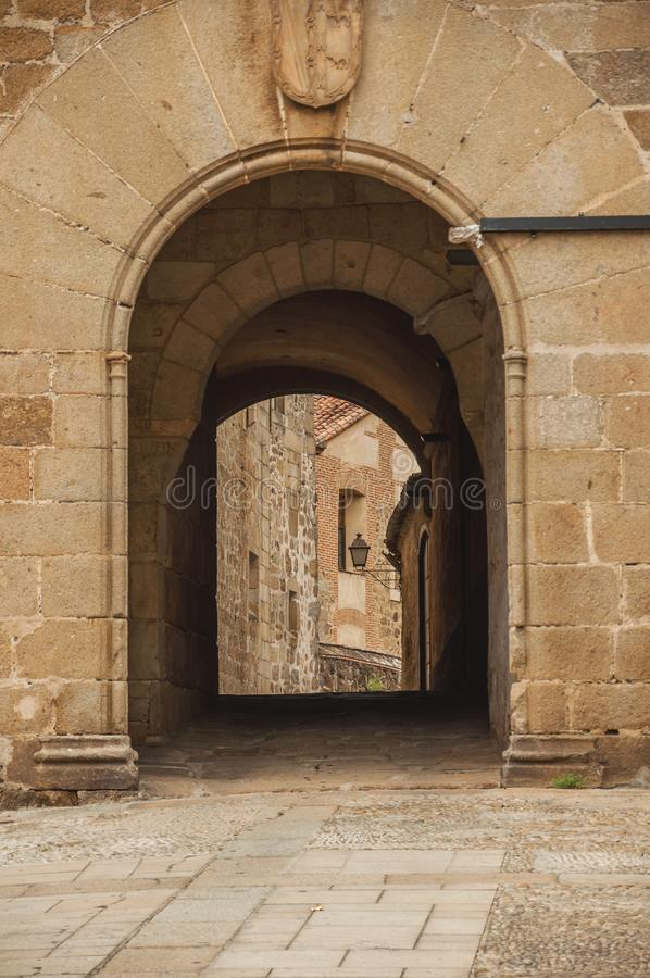 Arch gateway passing to an alley between gothic stone buildings in Plasencia royalty free stock image