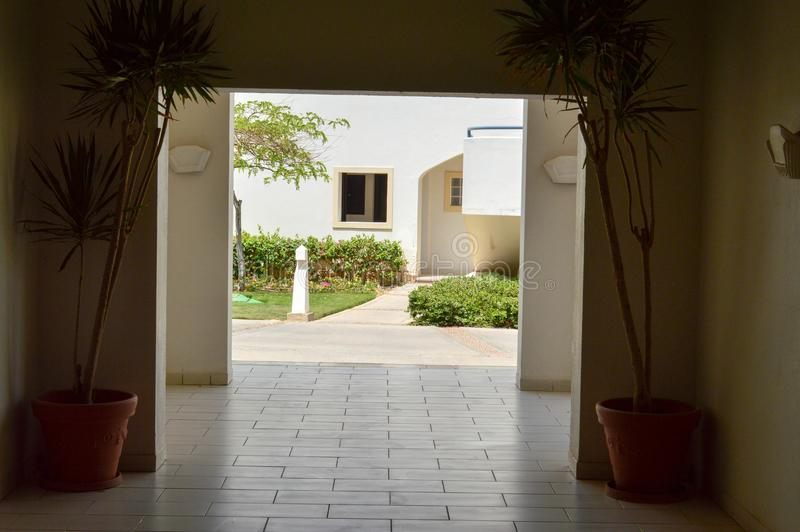 Arch inside, leaving the building with ceramic tiles on the floor in a hotel in a tropical resort and palm trees on the side royalty free stock photography