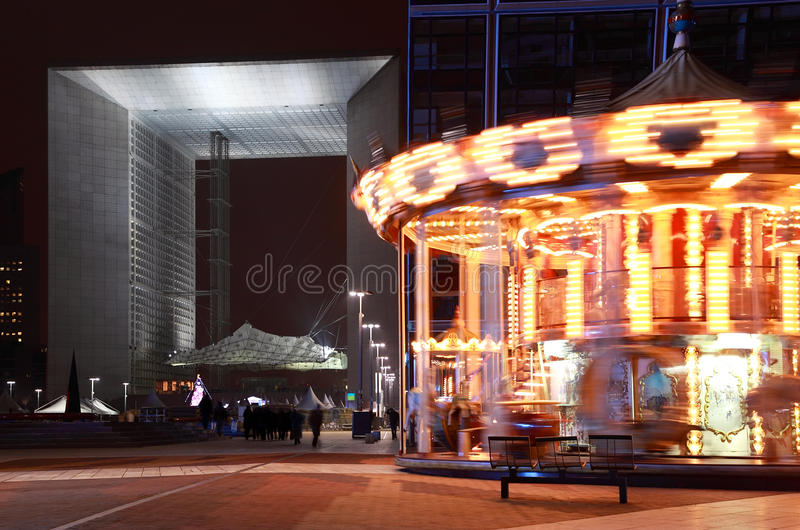 Arch of La Defense and whirling carousel in Paris