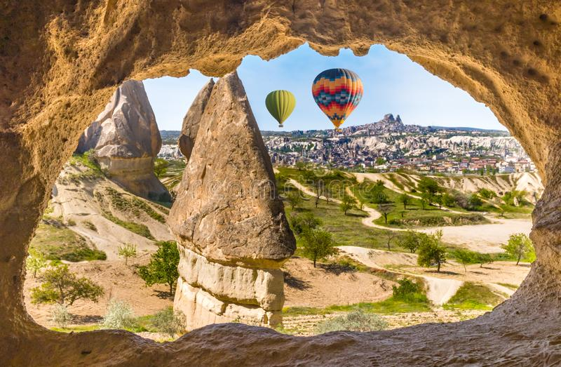 Arch in limestone in Goreme National Park, Cappadocia and hot air balloons. Hand carved arch in limestone rock in Goreme National Park, Cappadocia. Colorful hot stock photography