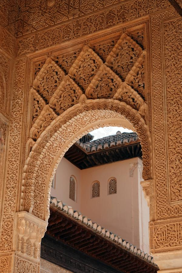 Arch at Lions court of Nasrid palace of the Alhambra in Granada, Andalusia. Wall decorations with arabesque ornaments at the Lions Palace of the Nasrid complex royalty free stock photography