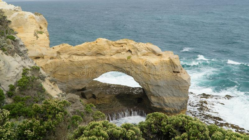 The Arch - naturally sculptured stone arch, one of many rock formations along The Great Ocean Road, Australia. The Arch - naturally sculptured stone arch, one of stock photography