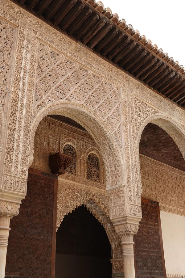 Arch of Palacio de Comares  at Nasrid palace  at the Alhambra in Granada, Andalusia. Wooden door and wall decorations with arabesque ornaments at the Palacio De royalty free stock photos