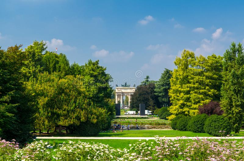 Arch of Peace gate and green trees, grass lawn in park, Milan, I. Arch of Peace Arco della Pace gate and green trees, flowers, grass lawn in Parco Sempione park stock photography