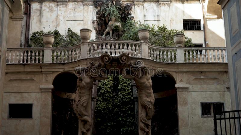 Arch with sculptures of ancient building. Action. Archway framed by statues leads to garden. Ancient european stock photo