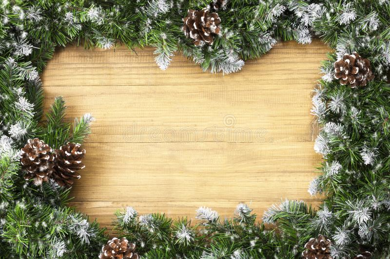 Arch shaped Christmas border composed of snow-covered fir branches and cones on christmas wooden background. Winter holiday. Background. Great for New year stock image