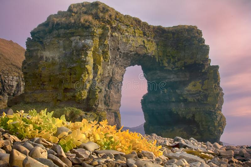 Arch of Steller. Massive stone arch. Arch of Steller (in honor of zoologist Georg Steller). Massive stone arch on shore of Pacific ocean. Bering Island stock photo